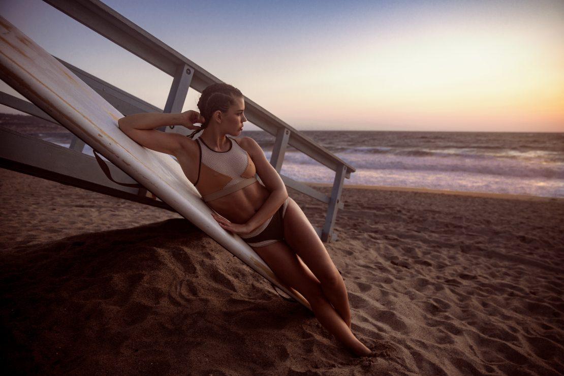 Schauspielerin und Model Anna-Lea Mende lehnt am Strand von Redondo Beach, Los Angeles an einem Surfbrett. Actress and model Anna-Lea Mende leaning on a surfboard at the beach of Redondo Beach, Los Angeles.