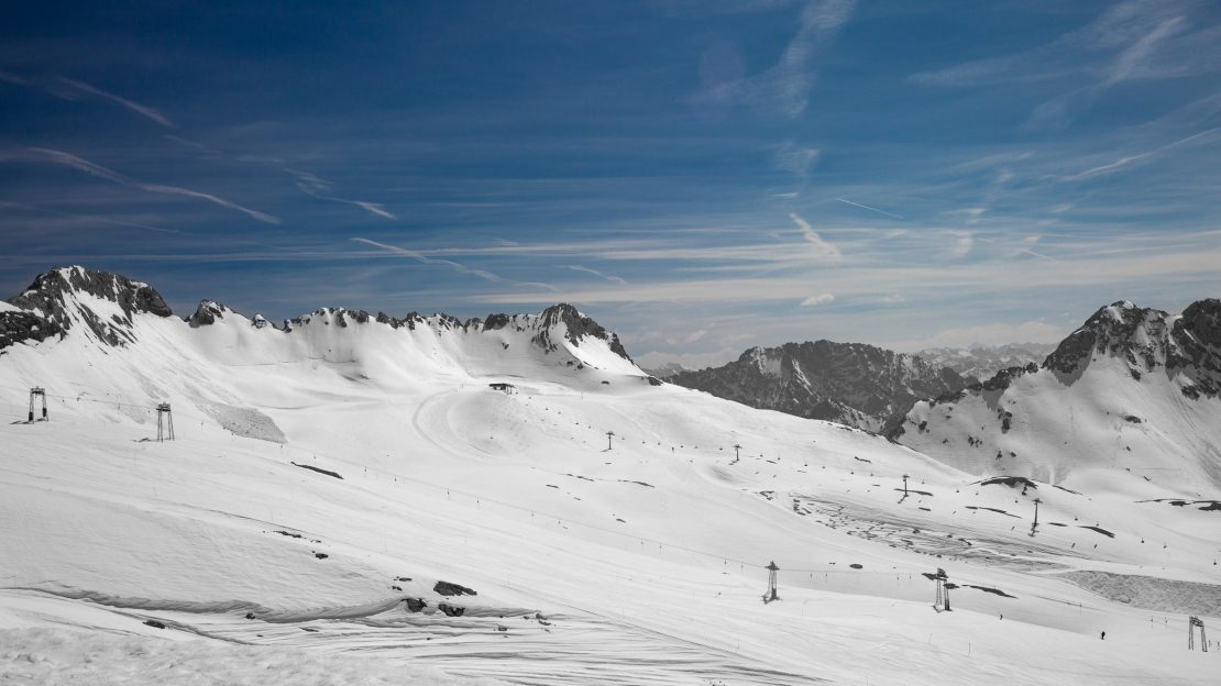 Alpenlandschaft mit schneebedeckten Bergen, Skiliften und blauem Himmel. Alps landscape with snowy mountains, skilifts and blue sky.