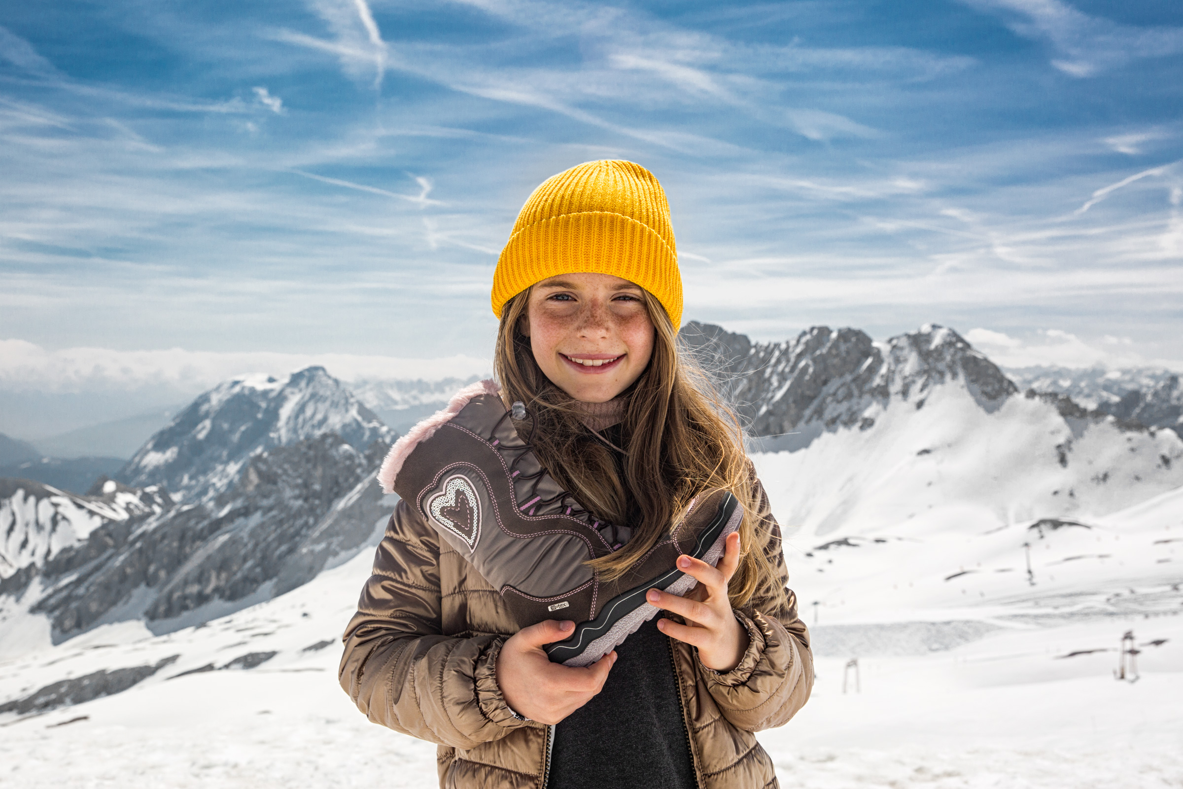Junges Mädchen hält Kinder-Schneeschuh an einem sonnigen Tag vor Alpenpanorama. Young girl holding a children's-snow-boot on a sunny day in front of alps landscape.