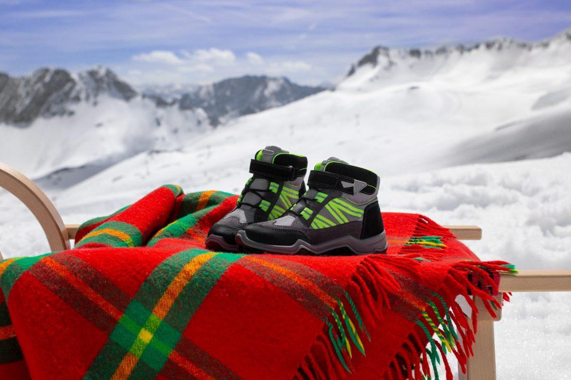 Kinderschuhe stehen auf einem mit einer roten Decke bezogenen Schlitten vor Alpenpanorama. Children's winter-footwear placed on a sledge that's covered with a red blanket in front of alps landscape.