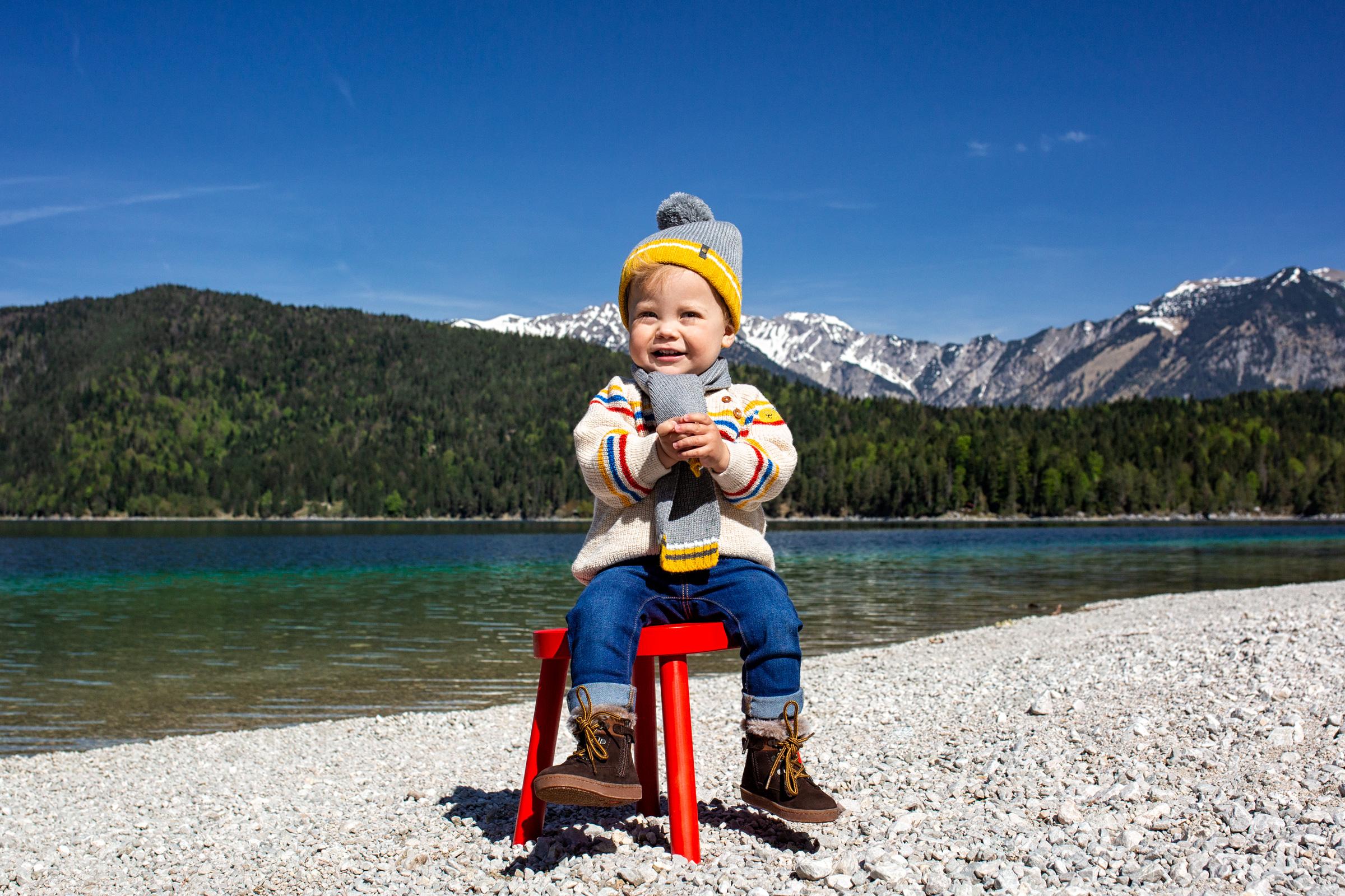 Kleiner Junge sitzt auf einem roten Stuhl am kiesbedeckten Ufer eines Alpensees. Little boy sits on a red chair at the gravelly beach of a tarn.