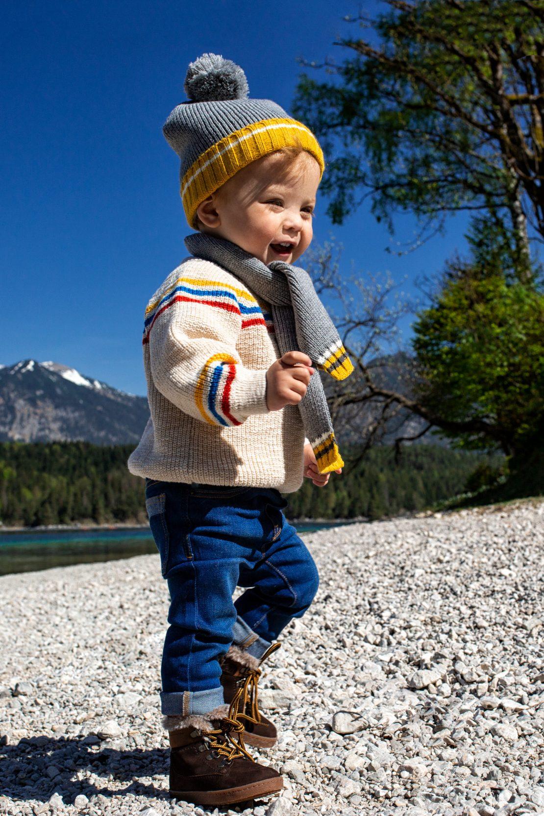 Kleiner Junge läuft am kiesbedeckten Ufer eines Alpensees. Little boy walks at the gravelly beach of a tarn.
