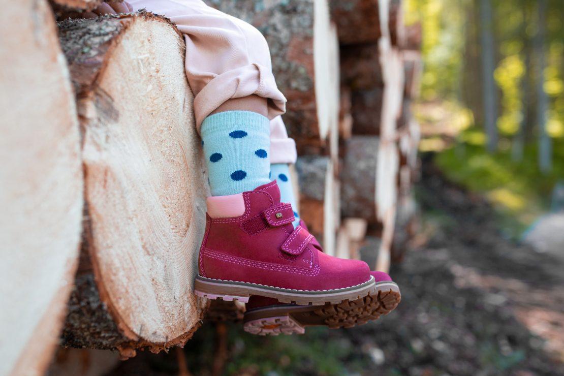 Nahaufnahme von Kinderschuhen eines auf Baumstämmen sitzenden Mädchens. Close-up of children's footwear of a girl that sits on tree trunks.