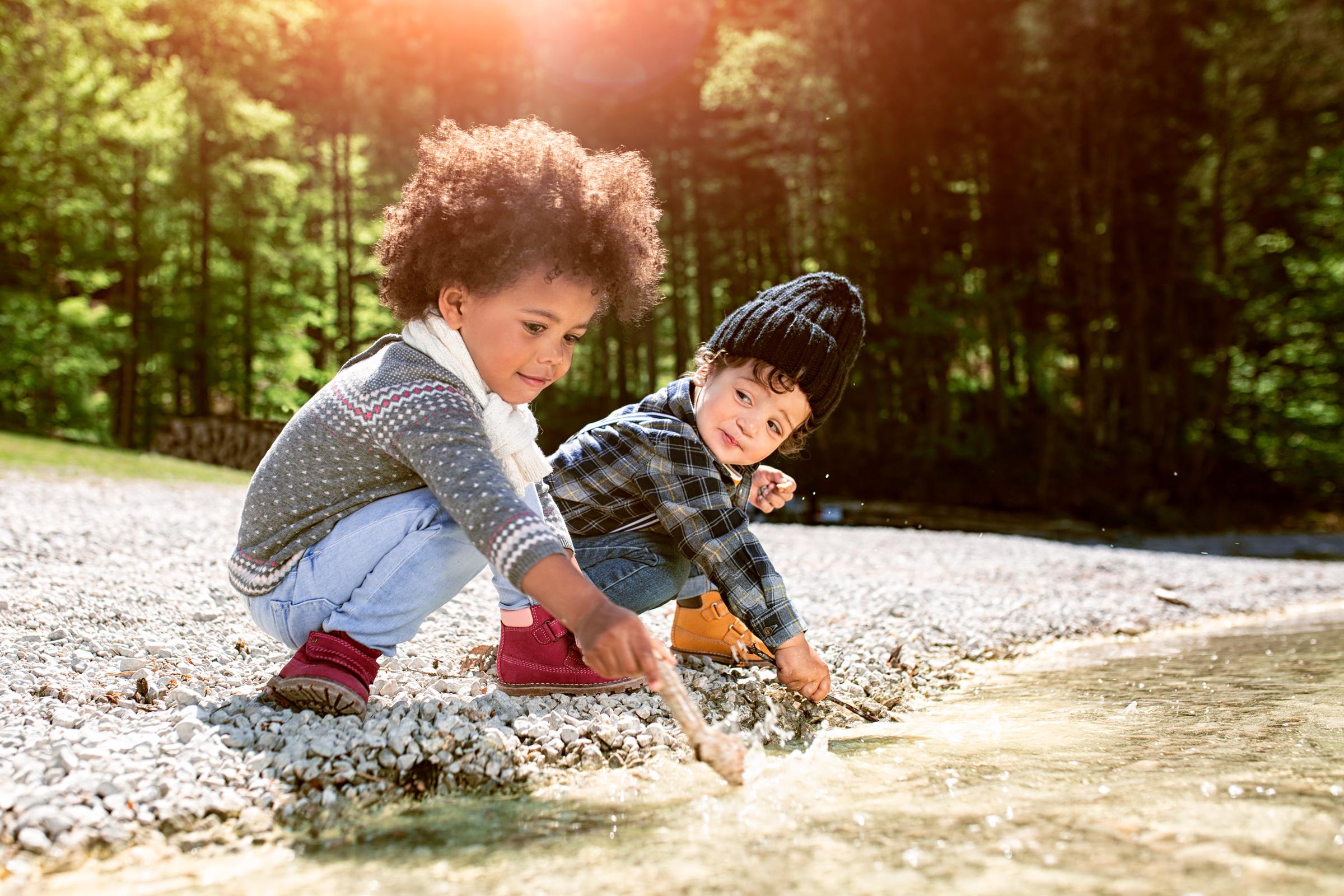 Zwei Kinder spielen am kiesbedeckten Ufer eines Alpensees. Two kids playing at the gravelly beach of a tarn.