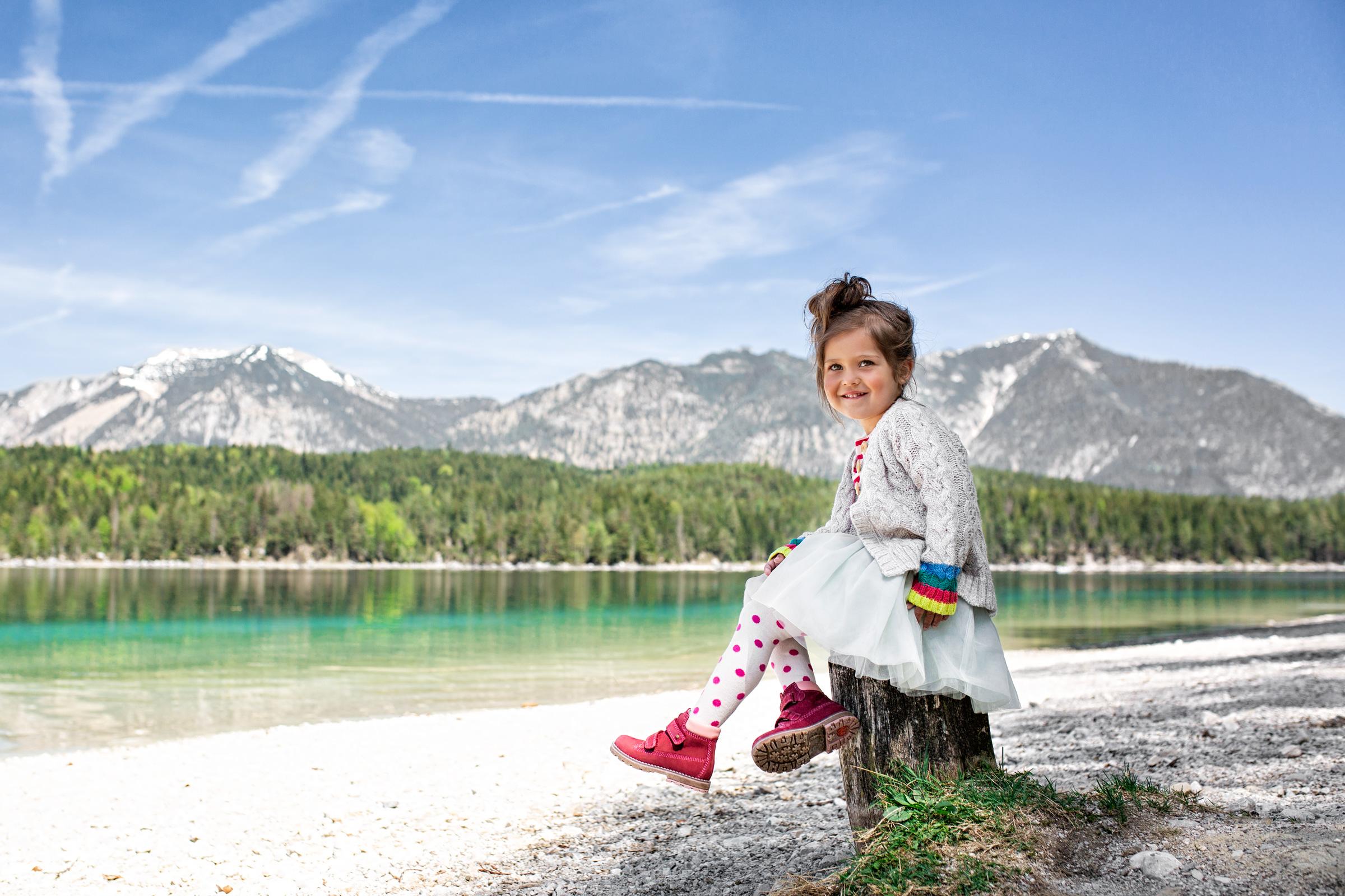 Ein Mädchen sitzt auf einem Baumstumpf am kiesbedeckten Ufer eines Alpensees. A girl is sitting on a tree trunk at the gravelly beach of a tarn.