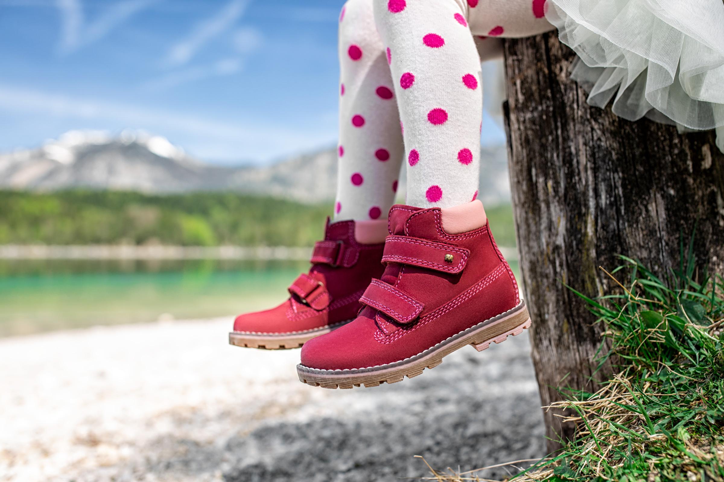 Nahaufnahme von Kinderschuhen eines auf einem Baumstumpf an einem Alpensee sitzenden Mädchens. Close-up of children's footwear worn by a girl sitting on a tree trunk at the at the gravelly beach of a tarn.