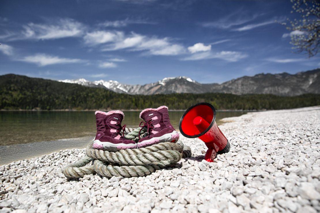 Produktaufnahme von auf einem Tau platzierten Kinderschuhen neben einem Megaphon am kiesbedeckten Ufer eines Alpensees. Productshot of children's footwear placed on a rope next to a megaphone at the gravelly beach of a tarn.