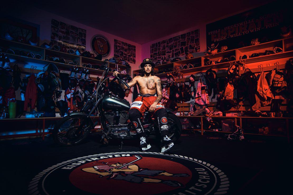Eishockey Stürmer sitzt oberkörperfrei auf seiner Harley in der Kabine. Ice Hockey player sits shirtless on his harley in the changing room.
