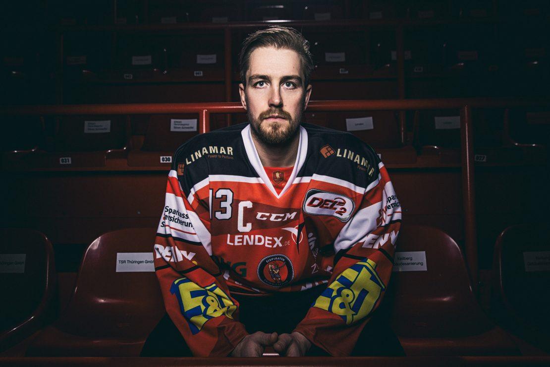 Eishockey Spieler sitzt mit fokussiertem Blick auf der Tribüne. Ice Hockey player sits with focussed look on the stand.