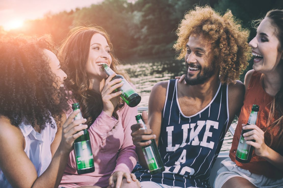 Junge Menschen trinken Moelmsch Bier auf einem Boot im Sonnenuntergang. Young people are drinking Moelmsch beer on a boat in the sunset.