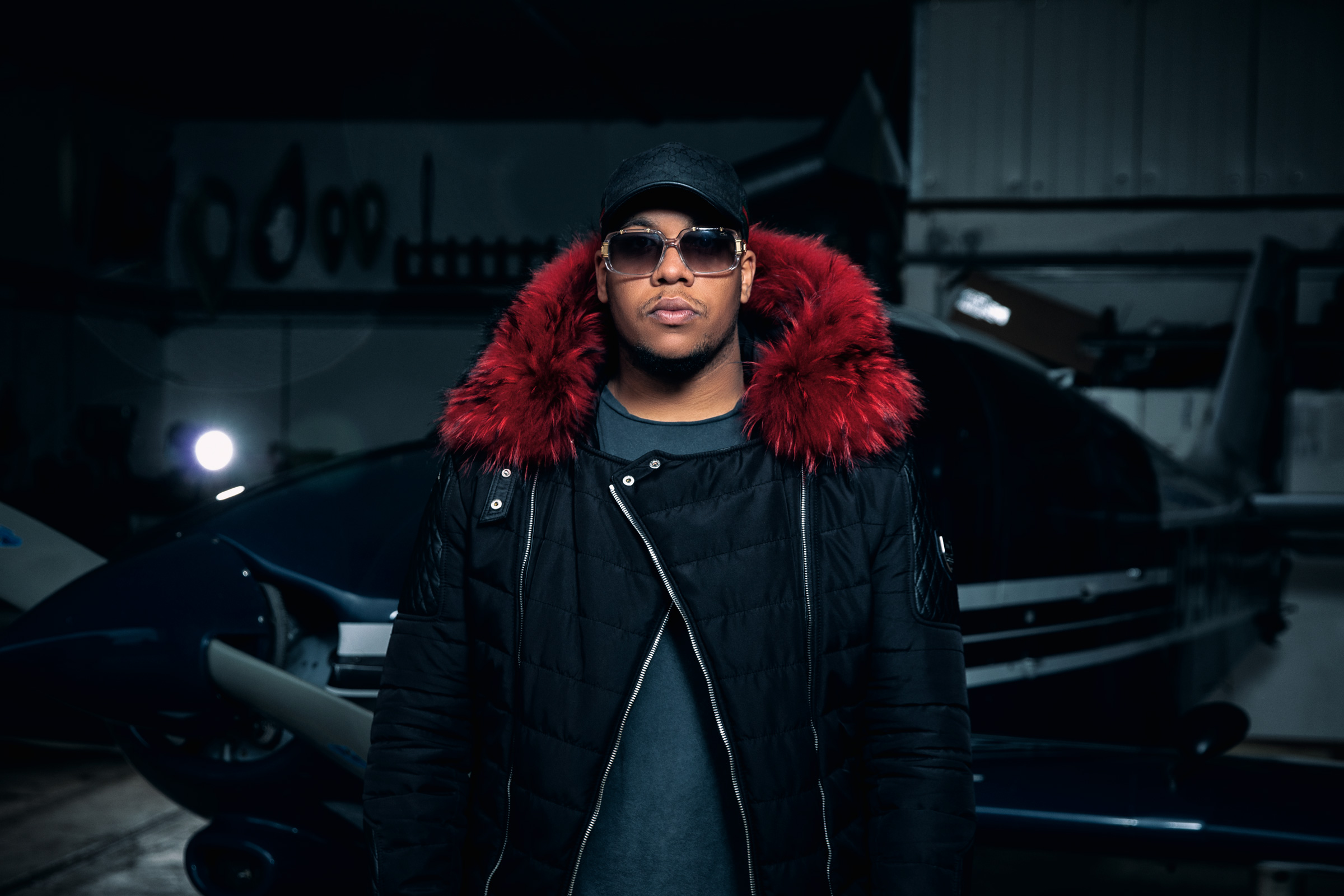 "Covermotiv des Deutschrappers NOIR zu seiner Single ""Horspist"". Noir steht in seiner Horspist-Jacke in einem Flugzeug-Hangar. Cover motiv of German rapper NOIRs single ""Horspist"". NOIR stands in a hangar wearing his Horspist jacket."