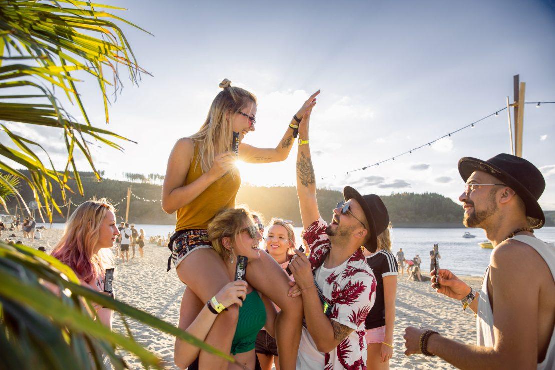Eine Gruppe Junger Menschen feiert am Festivalstrand und halten SUCKIT in ihren Händen. A couple of young people cheering at the festival beach holding SUCKIT in their hands.