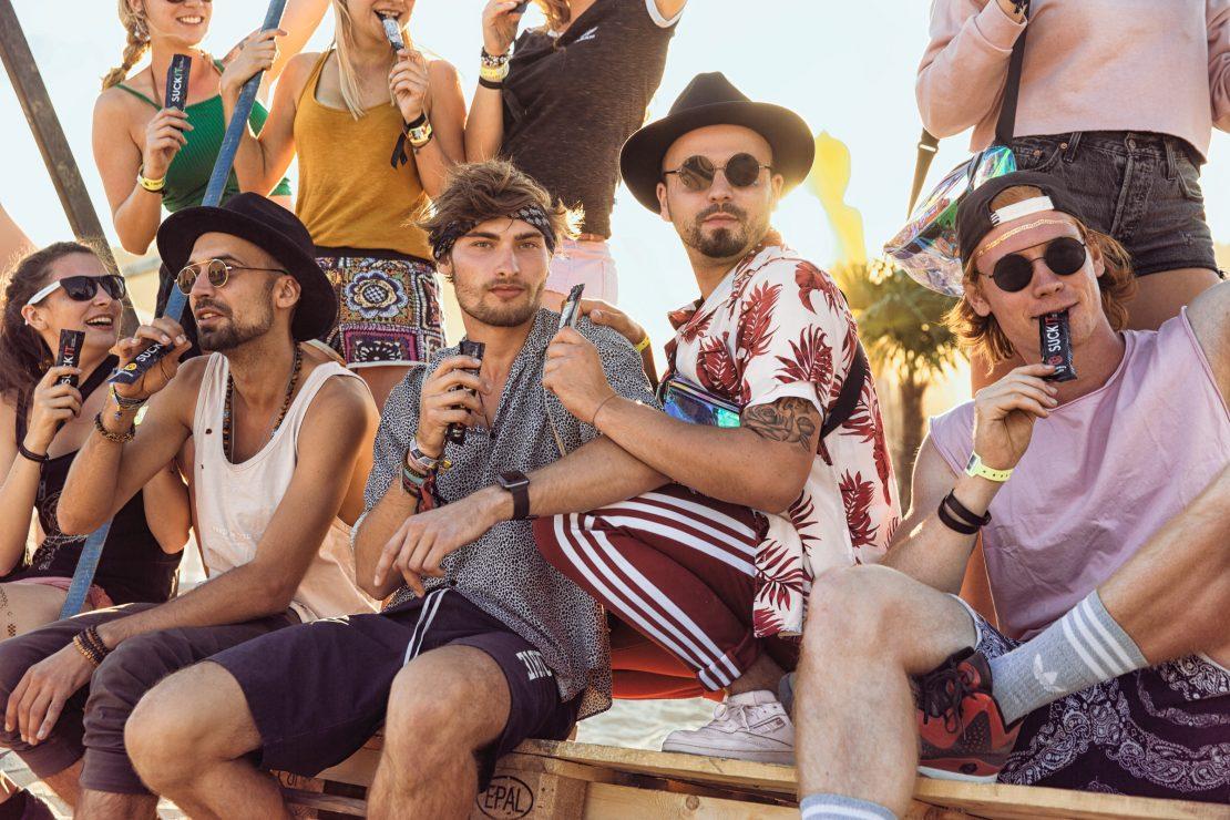 Eine Gruppe Junger Menschen sitzt auf einer großen Schaukel am Festival Strand und genießt dabei SUCKIT. A couple of young people are sitting on a swing at the Festival beach whilst enjoying their SUCKIT.