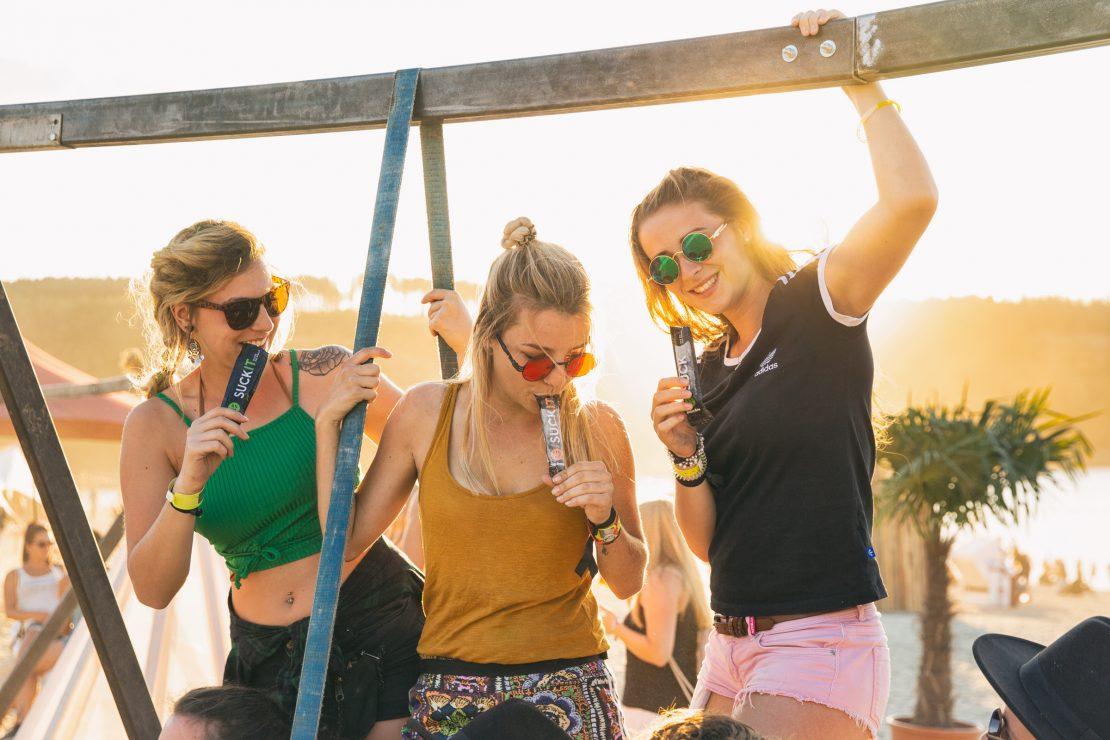 Drei junge Frauen stehen auf einer Schaukel am Festival Strand und genießen ihr SUCKIT. Three young women are standing on a swing at the festival beach enjoing their SUCKIT.
