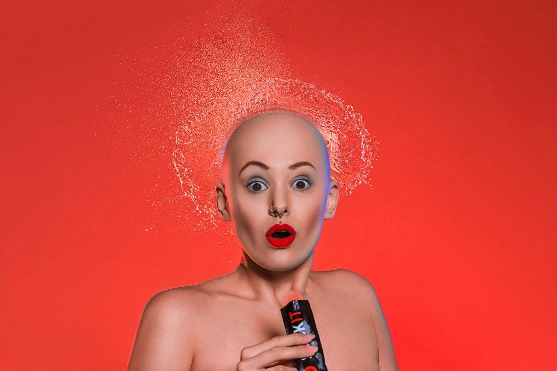 Studio-Portrait einer Frau mit Wasserexplosion über dem Kopf vor rotem Hintergrund. Studio portrait of a woman with a water explosion over her head in front of a red background.