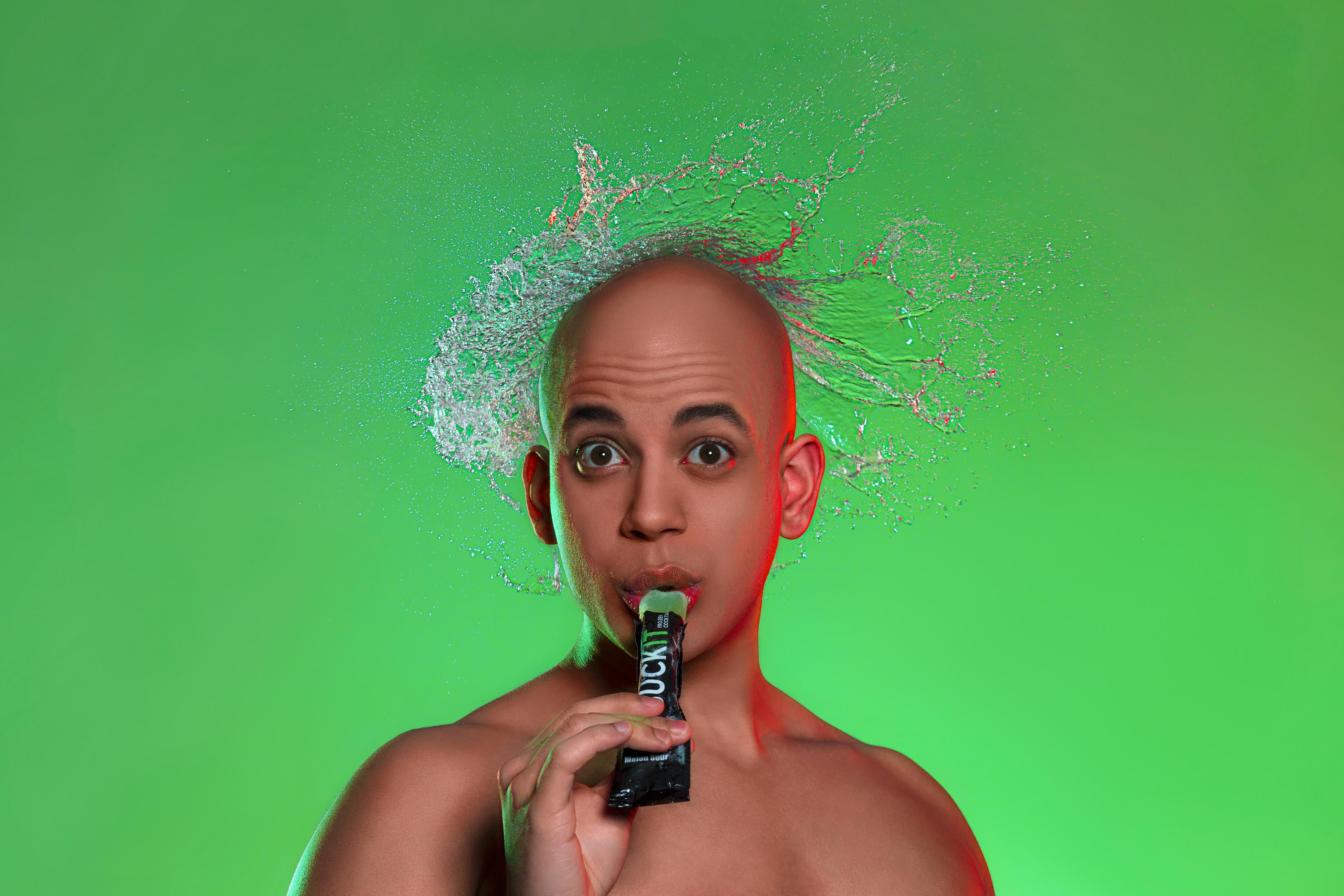 Studio-Portrait eines Mannes mit Wasserexplosion über dem Kopf vor gruenem Hintergrund. Studio portrait of a man with a water explosion over his head in front of a green background.