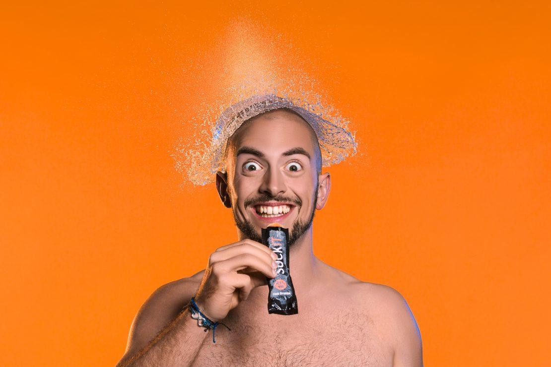 Studio-Portrait eines Mannes mit Wasserexplosion über dem Kopf vor orangenem Hintergrund. Studio portrait of a man with a water explosion over his head in front of a orange background.