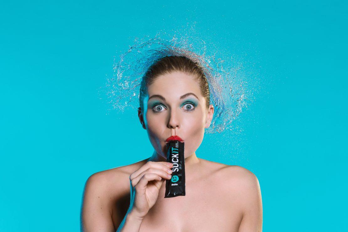 Studio-Portrait einer Frau mit Wasserexplosion über dem Kopf vor blauem Hintergrund. Studio portrait of a woman with a water explosion over her head in front of a blue background.