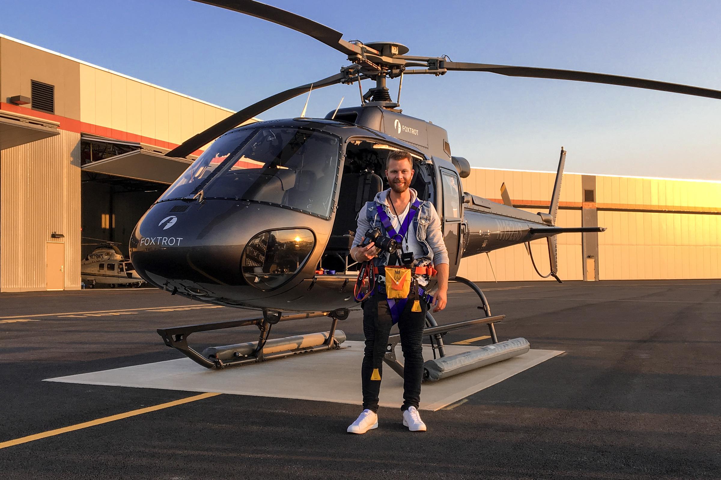 Portrait vom Fotografen Stephan Schmick vor einem Hubschrauber. Portrait of the photographer Stephan Schmick in front of a helicopter.